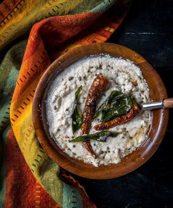 Coconut chutney served in a brown bowl tempered with red chilies and curry leaves.