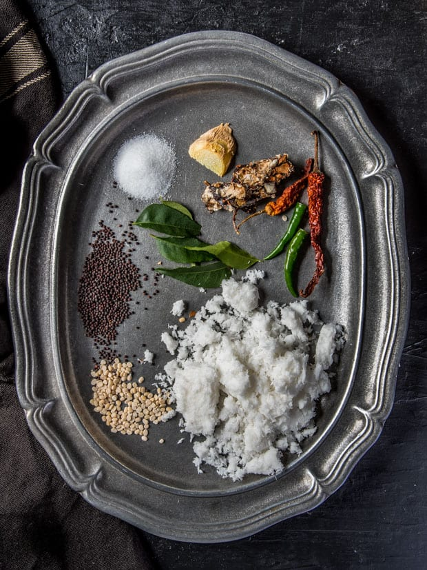 Ingredients used in coconut chutney - grated coconut, green chilies, red chili, tamarind, ginger, salt, curry leaves, mustard seeds, and urad dal
