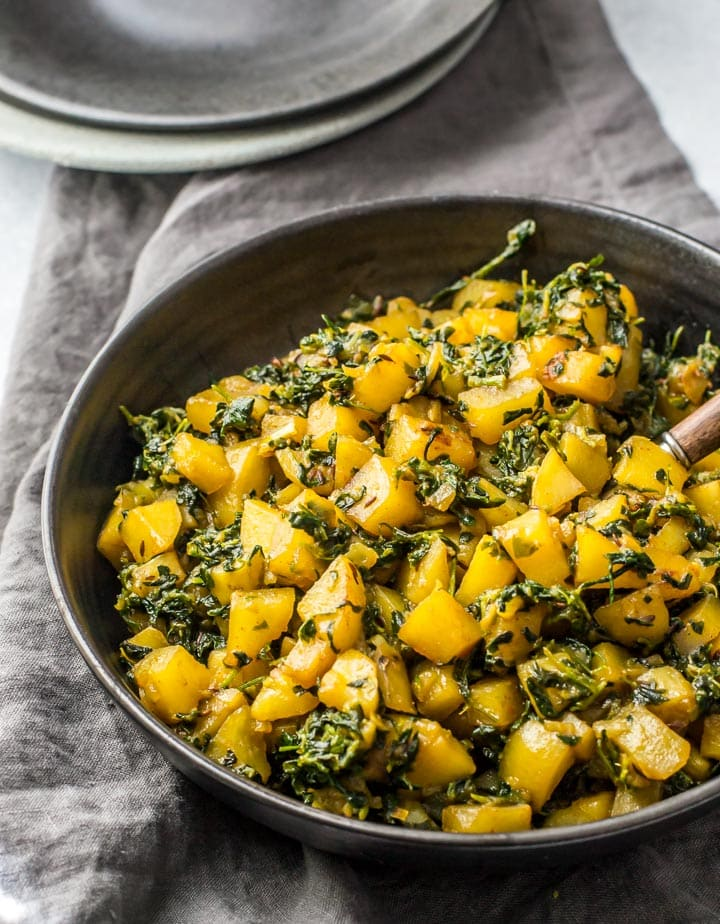 Aloo methi served in a black bowl along with a grey napkin