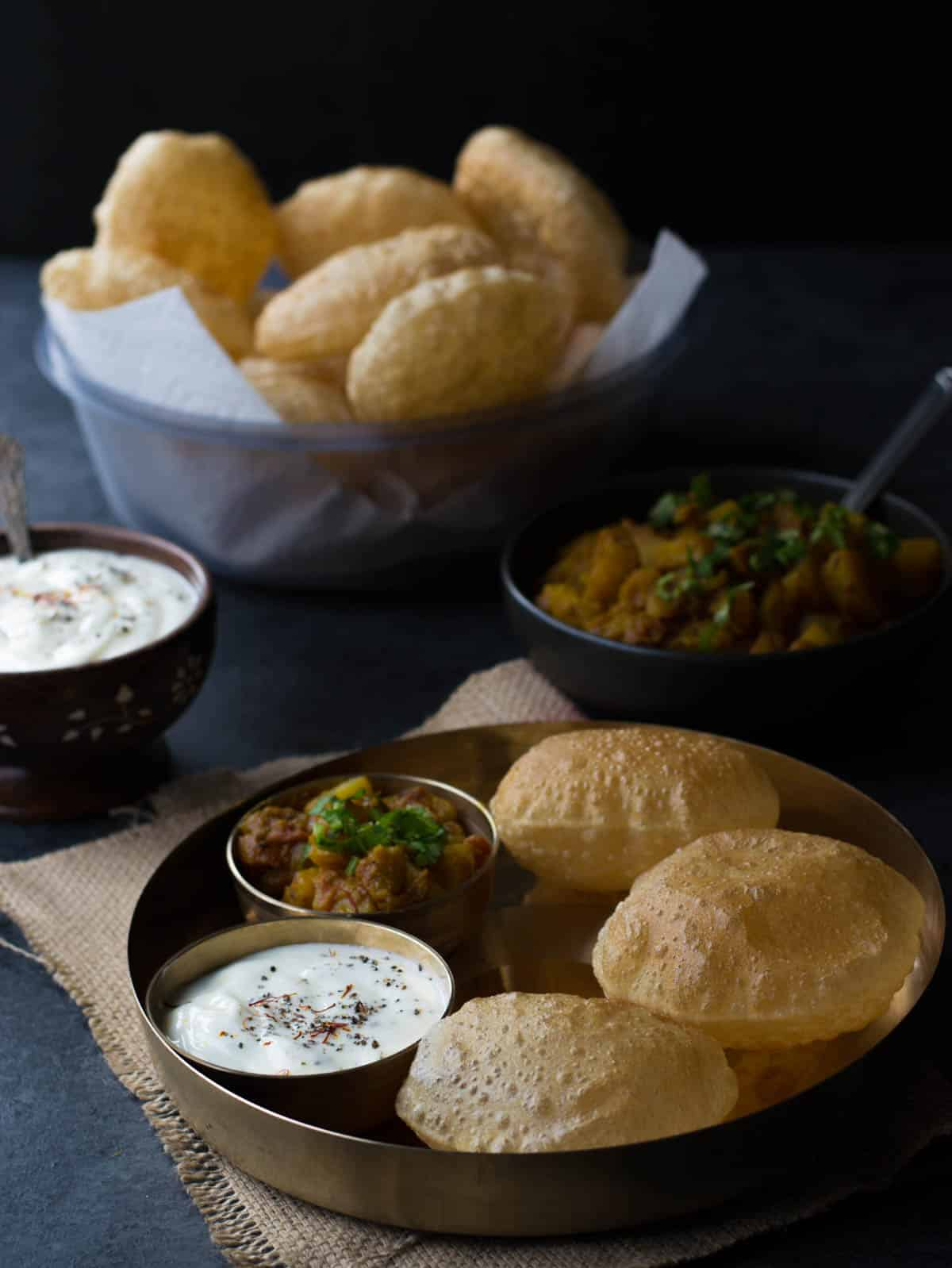 Poori, Shrikhand and Potato vegetable dish served in a golden plate.