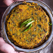 Methi thepla served on a metal plate with green chilies on top