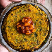 Methi thepla served in a metal plate with chundo on top