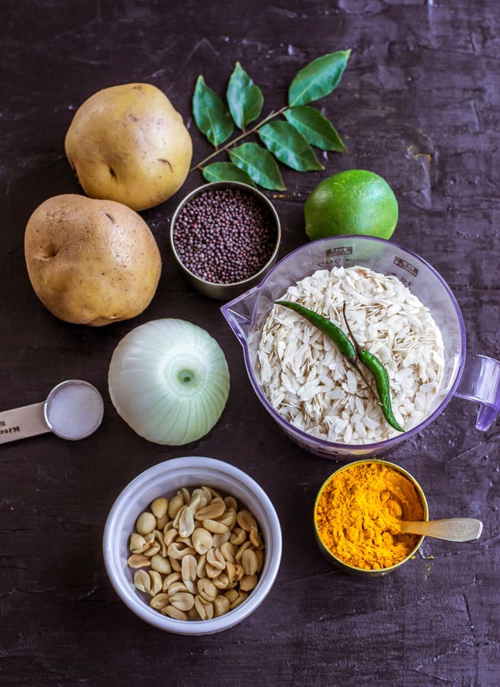 Shows ingredients for Poha - curry leaves, potatoes, mustard seeds, onions, salt, peanuts, turmeric powder, lemon, green chilies and poha