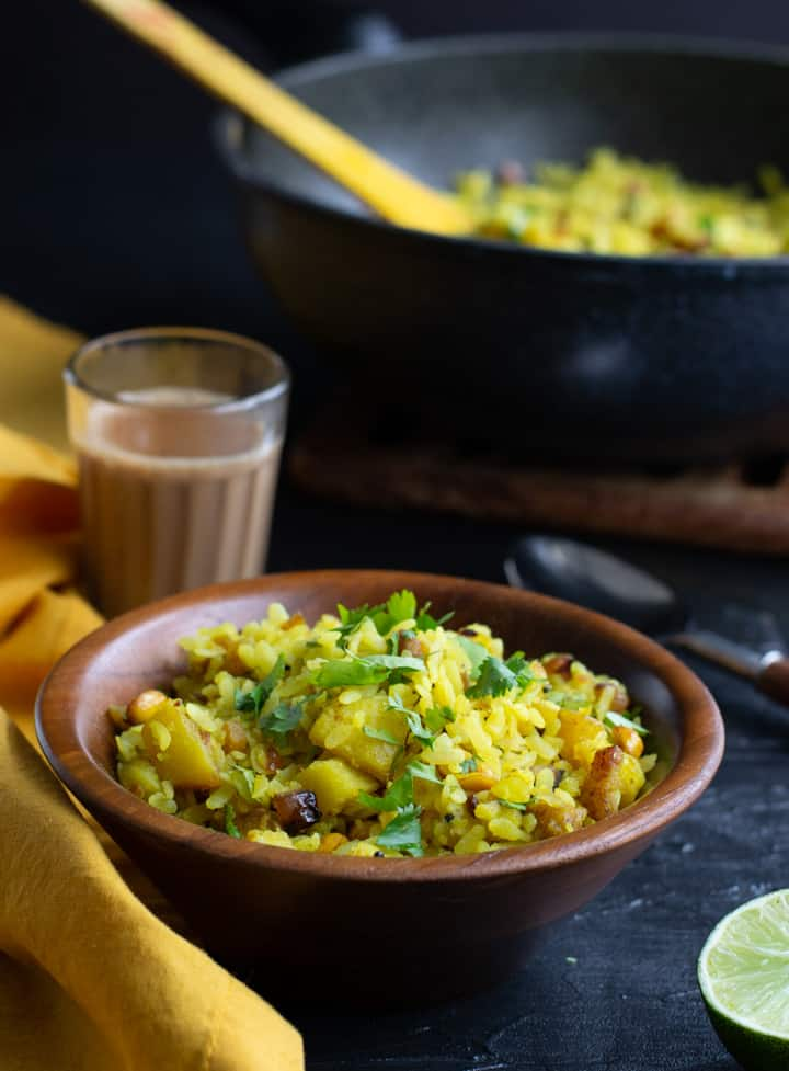 Poha served in a wooden bowl and served with tea. Yellow napkin as well as half a lemon is in the background as well