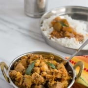Bareda kai ajadina served in a steel bowl. It is accompanied by a glass of water and a steel plate with rice and curry