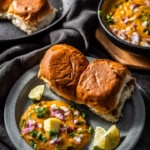 Pav bhaji served with a silver of butter, finely chopped onions, crispy pav and lemon wedges