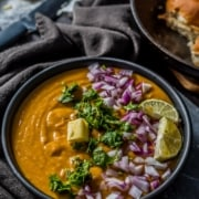 Instant Pot Pav bhaji served with a silver of butter, finely chopped onions, and lemon wedges in a black bowl