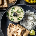 An overhead shot of Gujarathi kadhi along with rice, rotis and a side of lemon