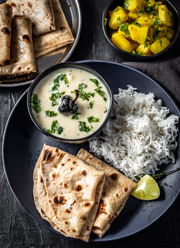 An overhead shot of Gujarathi kadhi along with rice, rotis and a side of lemon