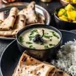 Gujarathi kadhi is served along with rice, rotis and a side of lemon