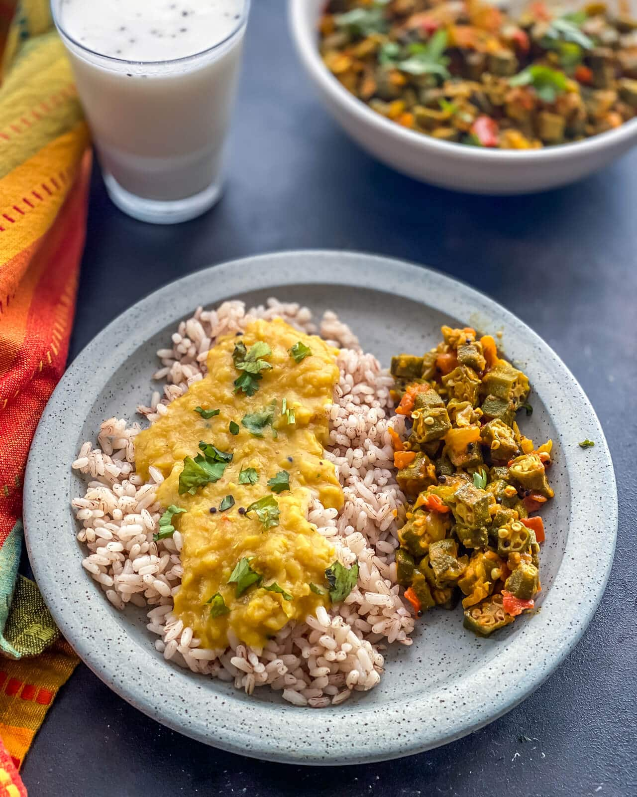 Bhindi subzi served with rice and dal in a grey plate