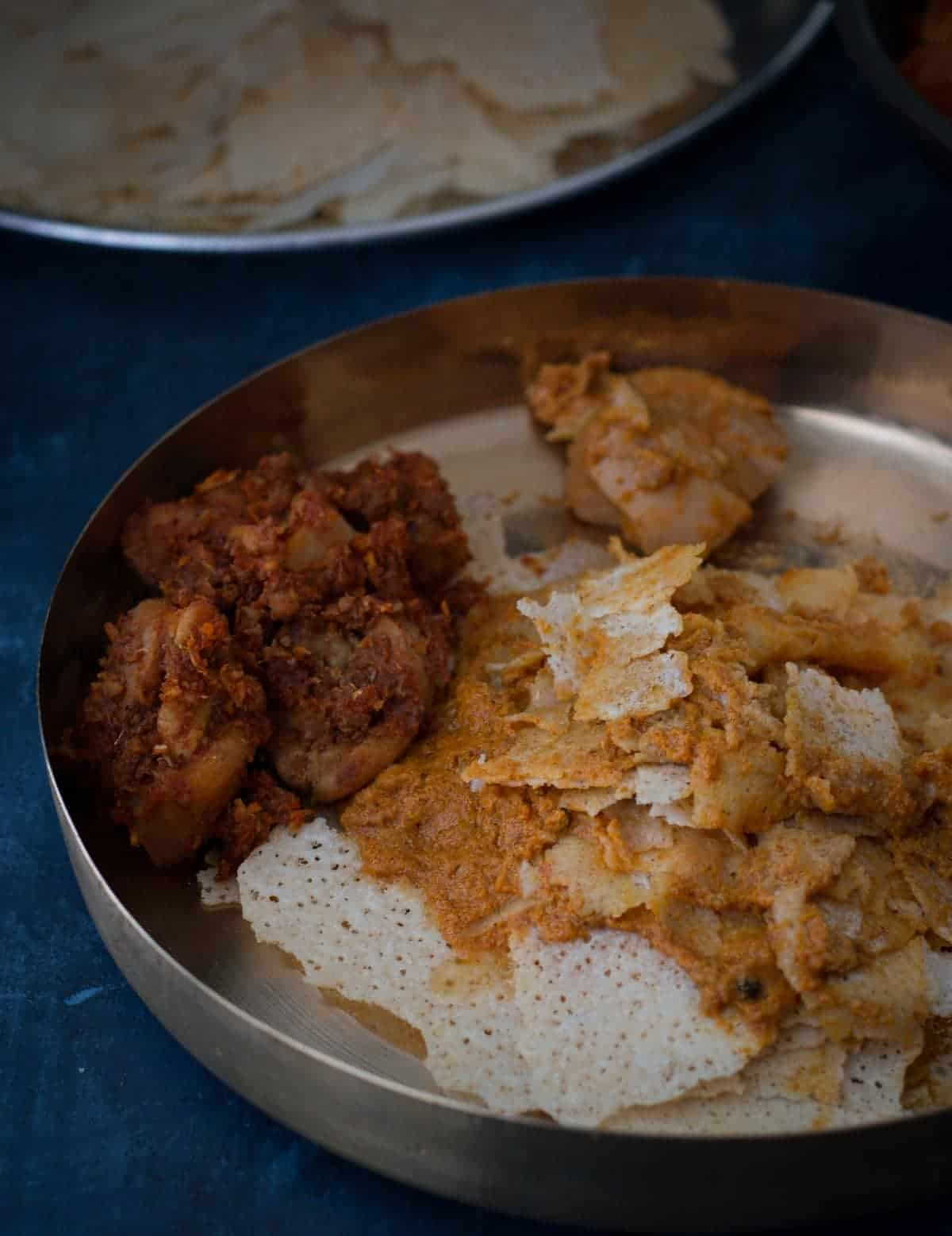 Kori Gassi served with Rutti (crispy thin rice wafers) are like match made in heaven. It is served in a bronze plate along with dry chicken dish (Kori ajadina)