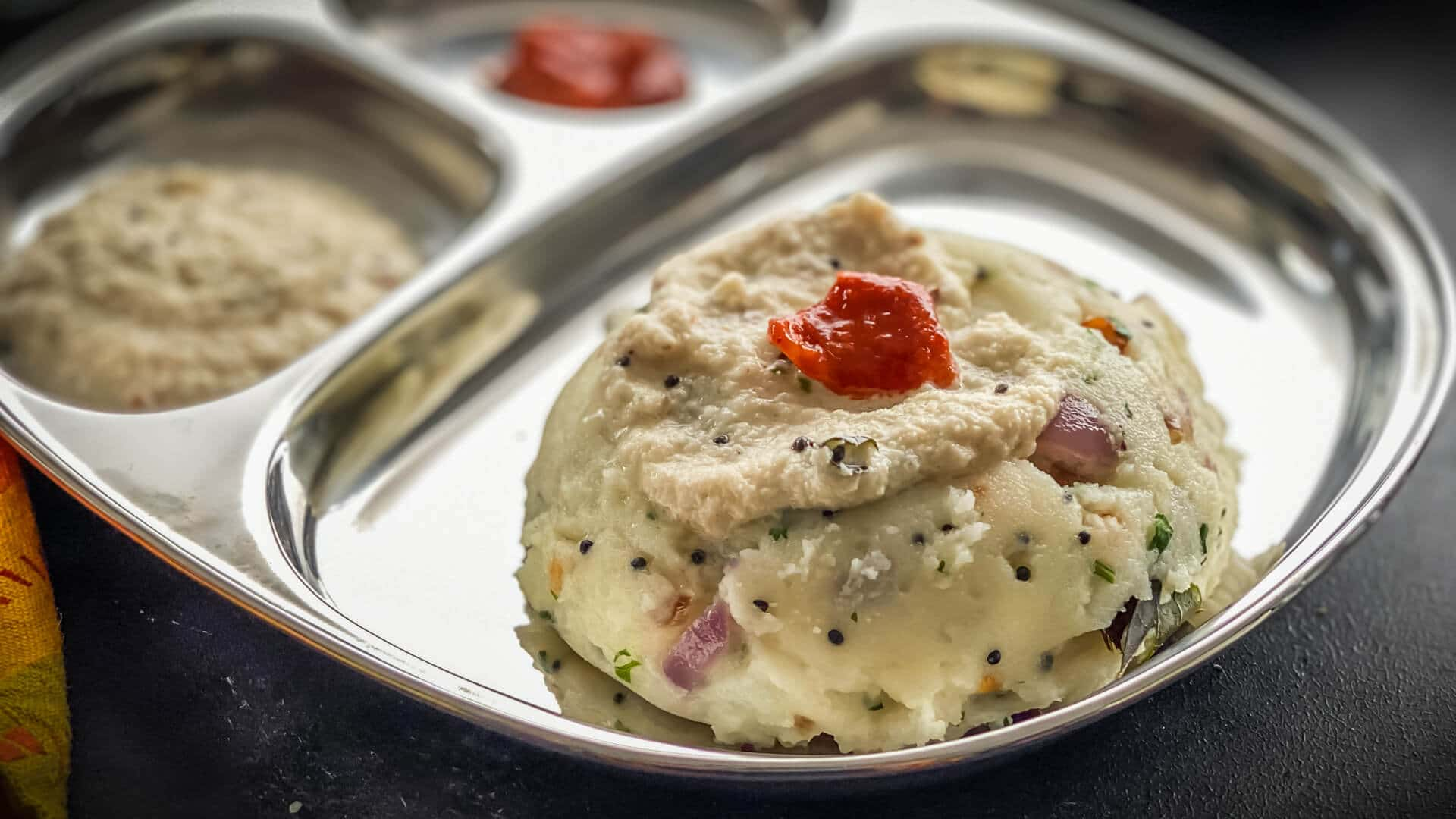 Rava upma served in a steel plate along with cooconut chutney and pickle