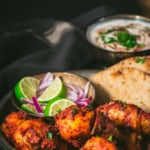 Tandoori chicken is served with a side of lemon wedges, sliced onions and naan