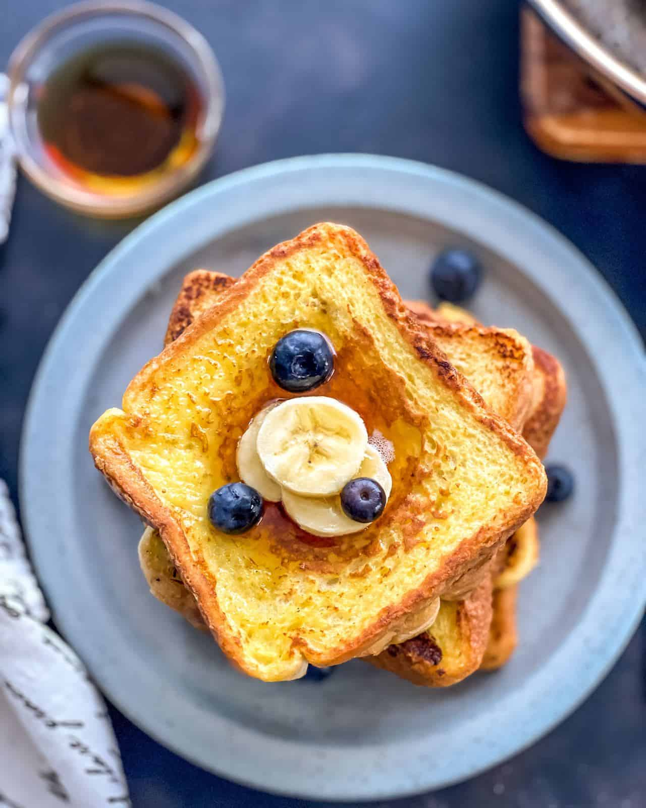 A blue plate of french toast shot from the top down with slices of banana and blueberries on top and a small bowl of syrup to the top left of the plate.