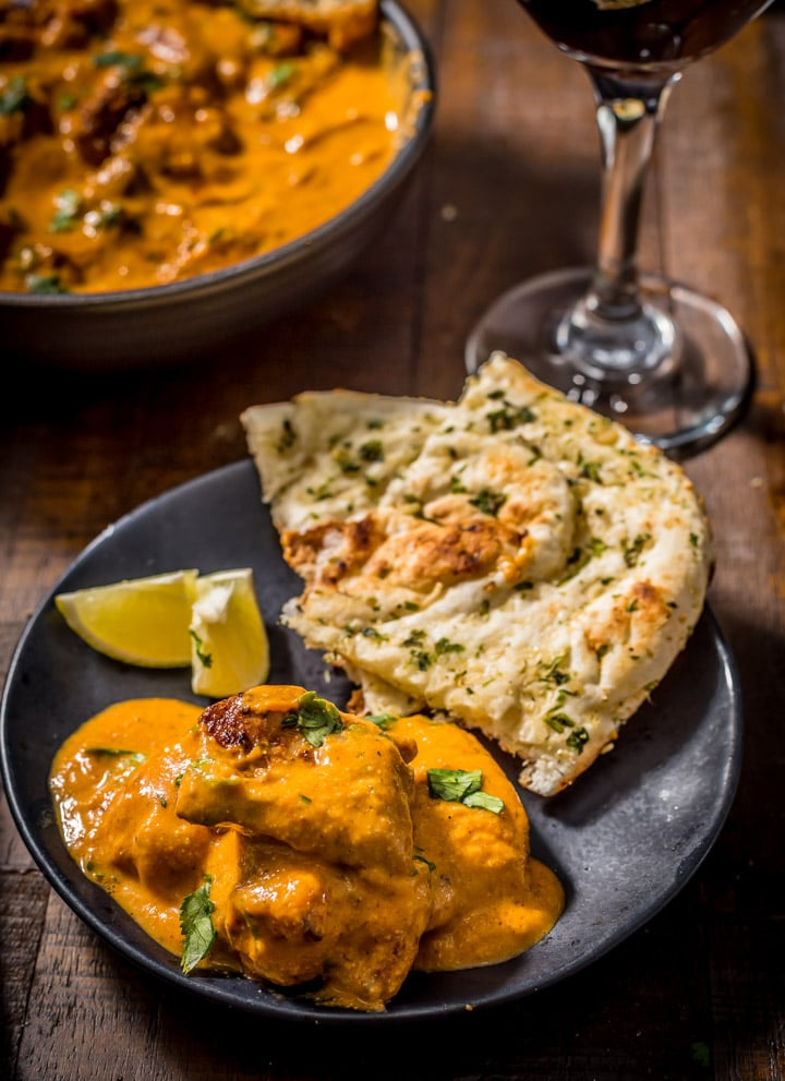 An overhead shot of chicken tikka masala served in a black plate with garlic naan