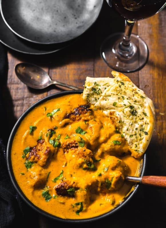 Chicken Tikka Masala served in a black bowl with garlic naan dipped in it