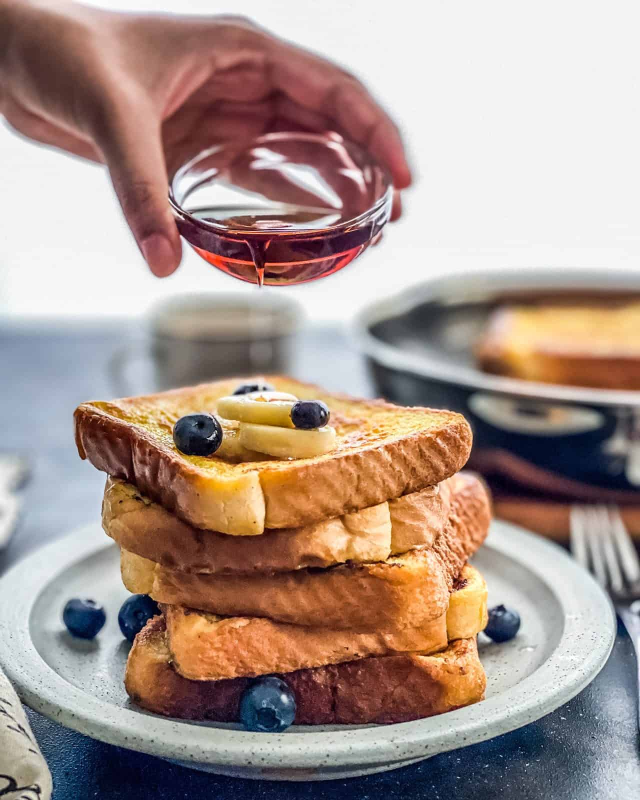 A fresh stack of french toast on a blue plate with a hand pouring syrup on top of the stack.
