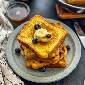 A blue plate with a stack of french toast with blueberries and banana slices on top and a small bowl of syrup in the background.