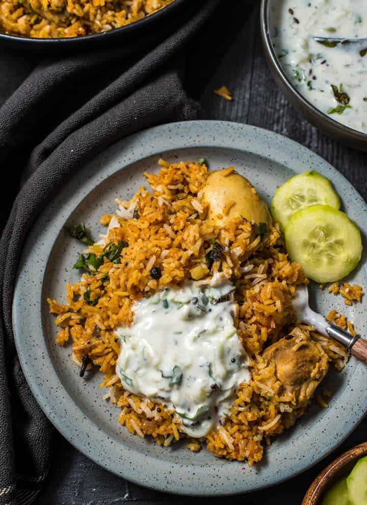 An overshot of biryani served with cucumber raita and a few slices of cucumber on a gray plate