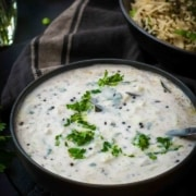 Cucumber raita served in a black bowl accompanied by jeera rice in a black bowl along with a black napkin on the side