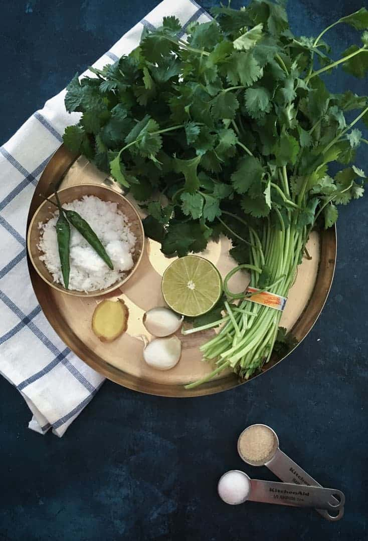 Coriander chutney ingredients laid out - coriander/cilantro leaves, 1/2 lime, garlic, ginger, grated coconut, sugar and salt