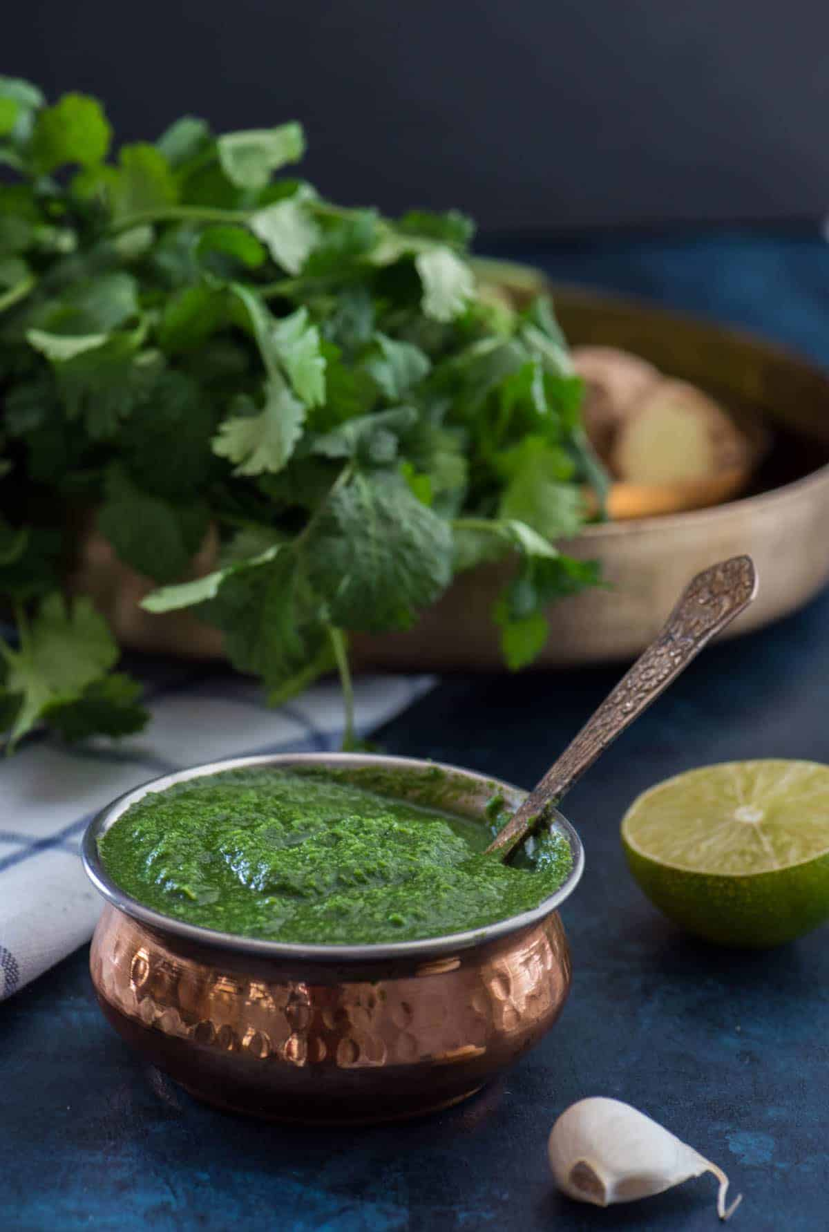 Green chutney served in a copper bowl. Also shown are the ingredients for coriander chutney - 1/2 of lime, garlic, coriander/cilantro leaves