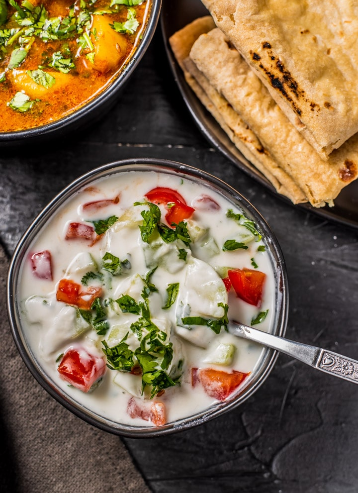 Cucumber tomato raita served in a black bowl and is accompanied by rotis and a bowl of potato curry