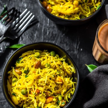Lemon Semiya Upma served in a black bowl with a glass of tea
