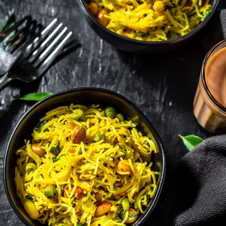 Lemon Semiya Upma served in a black bowl with a glass of tea