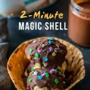 The words 2 minute magic shell in the top of the photo with a waffle cone bowl with vanilla ice cream topped with magic shell sauce and sprinkles on a dark counter.