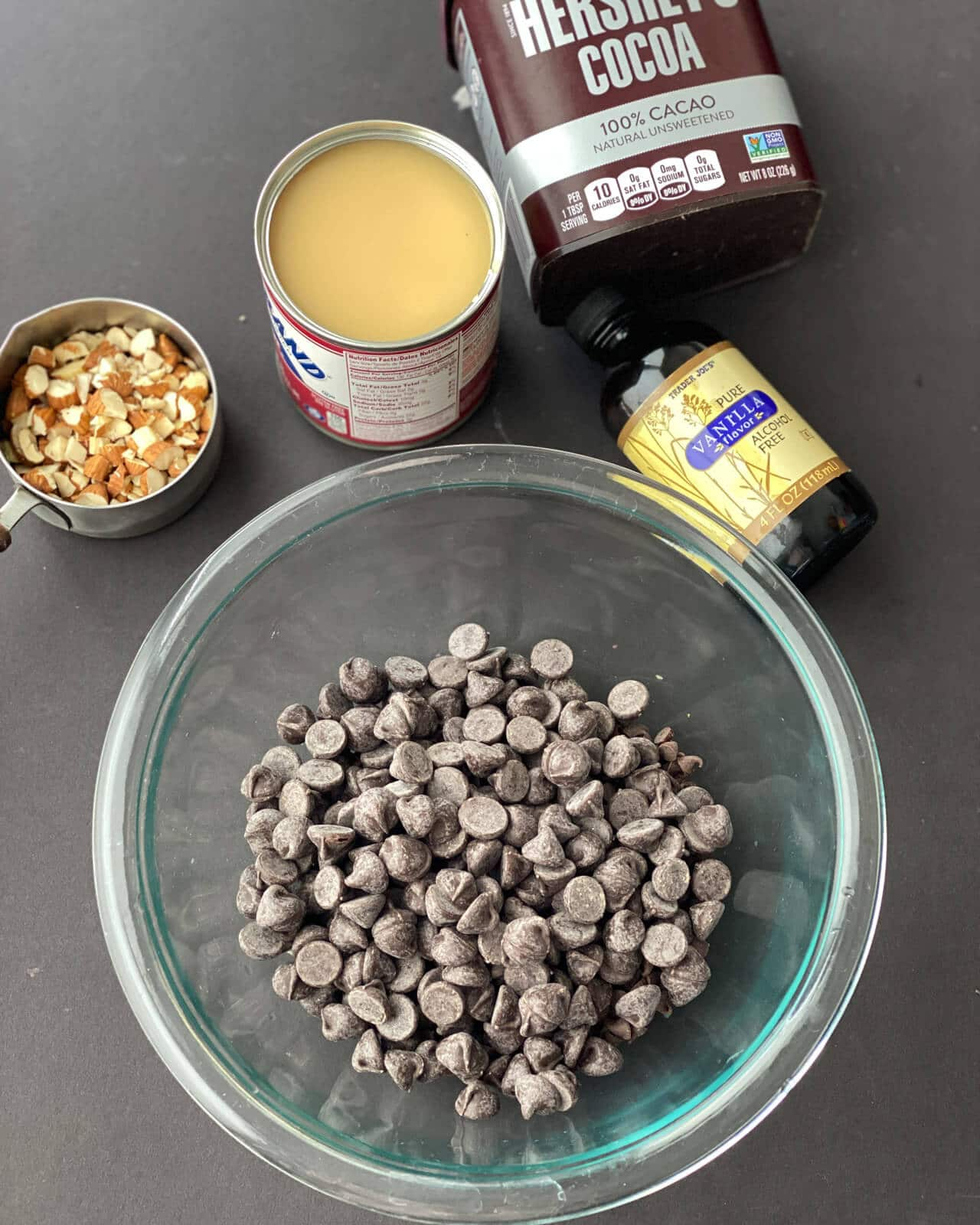 chocolate chips in a glass bowl with vanilla essence, chopped almonds, condensed milk and cocoa powder on the side