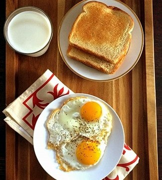 An overhead shot of a tray holding two half fried eggs served on a white plate accompanied by a glass of milk and 2 slices of toasted bread.