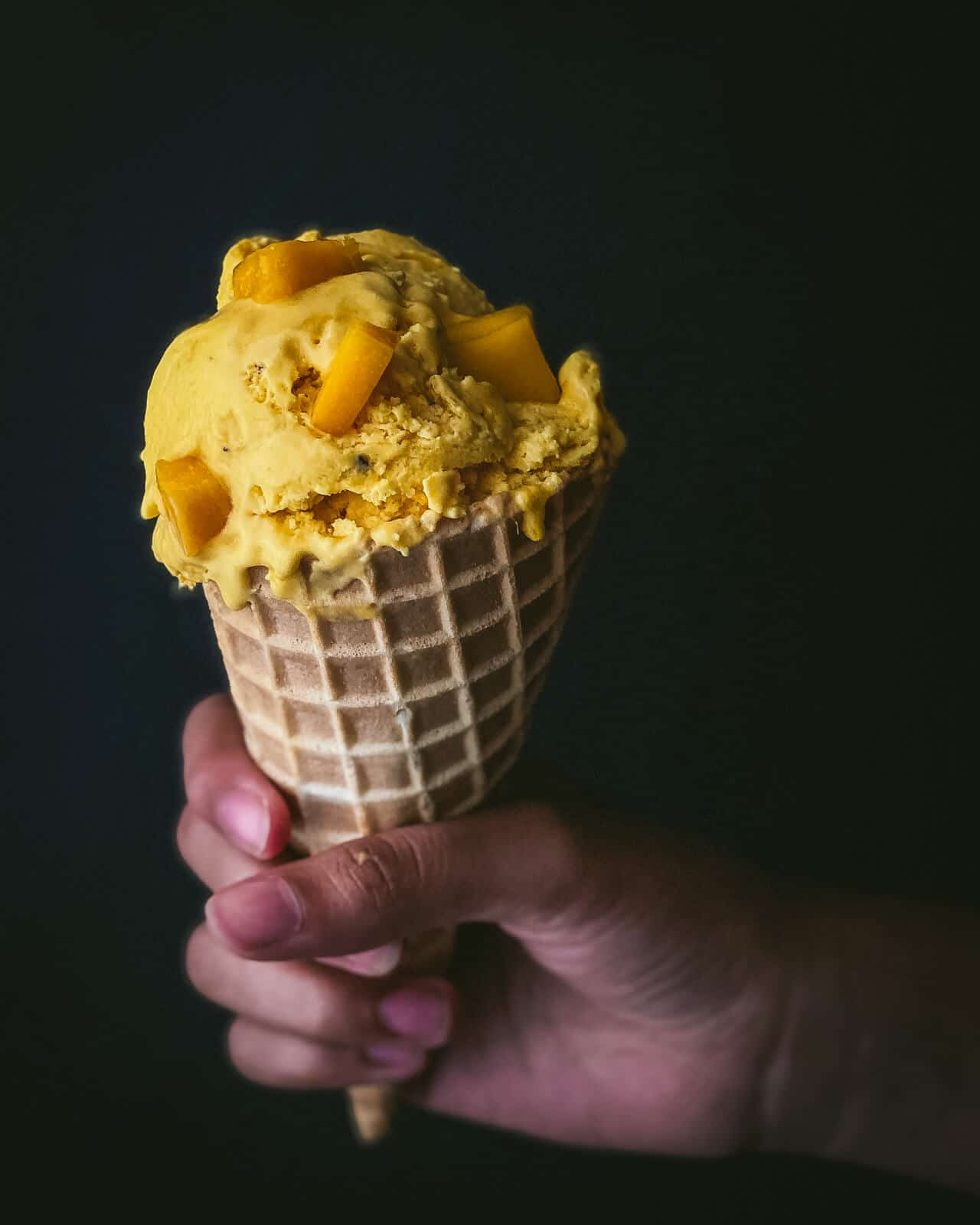 A hand holding a cone filled with mango ice cream