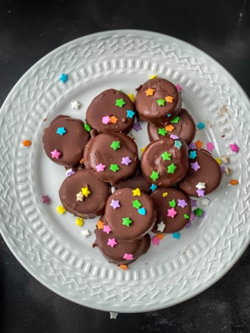 Frozen chocolate covered banana bites served on a white plate