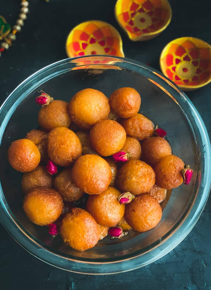 A clear bowl filled with gulab jamun balls on a dark counter with three yellow bowls in the top right.