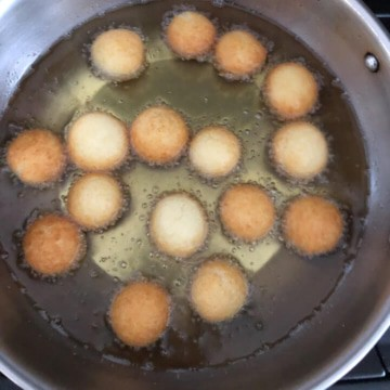 Many dough balls frying in the oil.