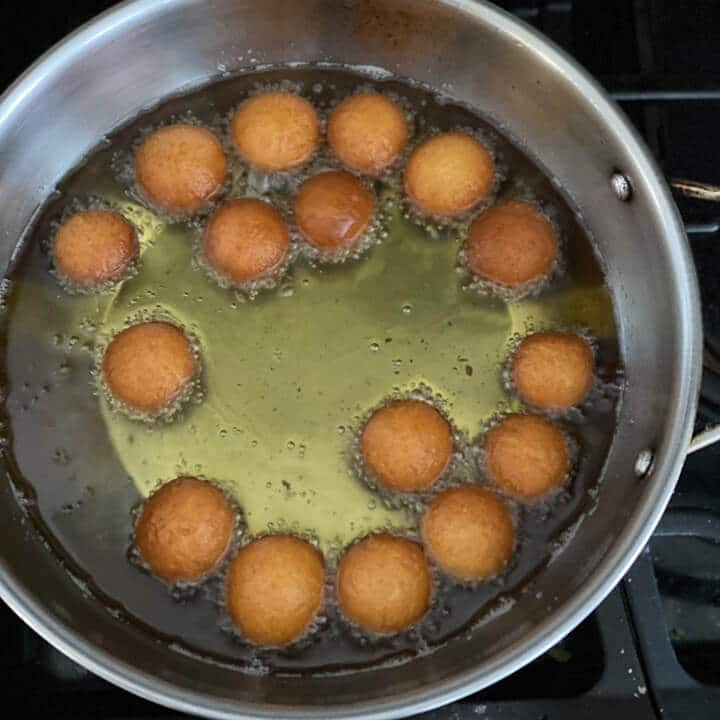 Gulab jamun frying on the other side in the pan.
