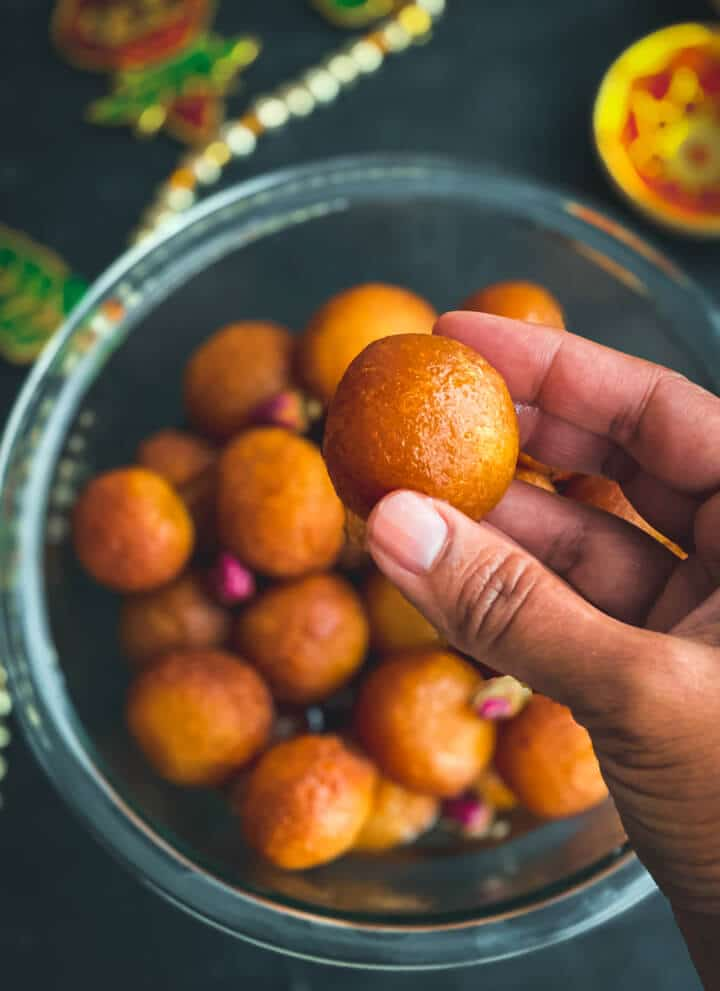 A glass bowl of milk powder gulab jamun balls on a dark counter with a hand in front holding a gulab jamun.
