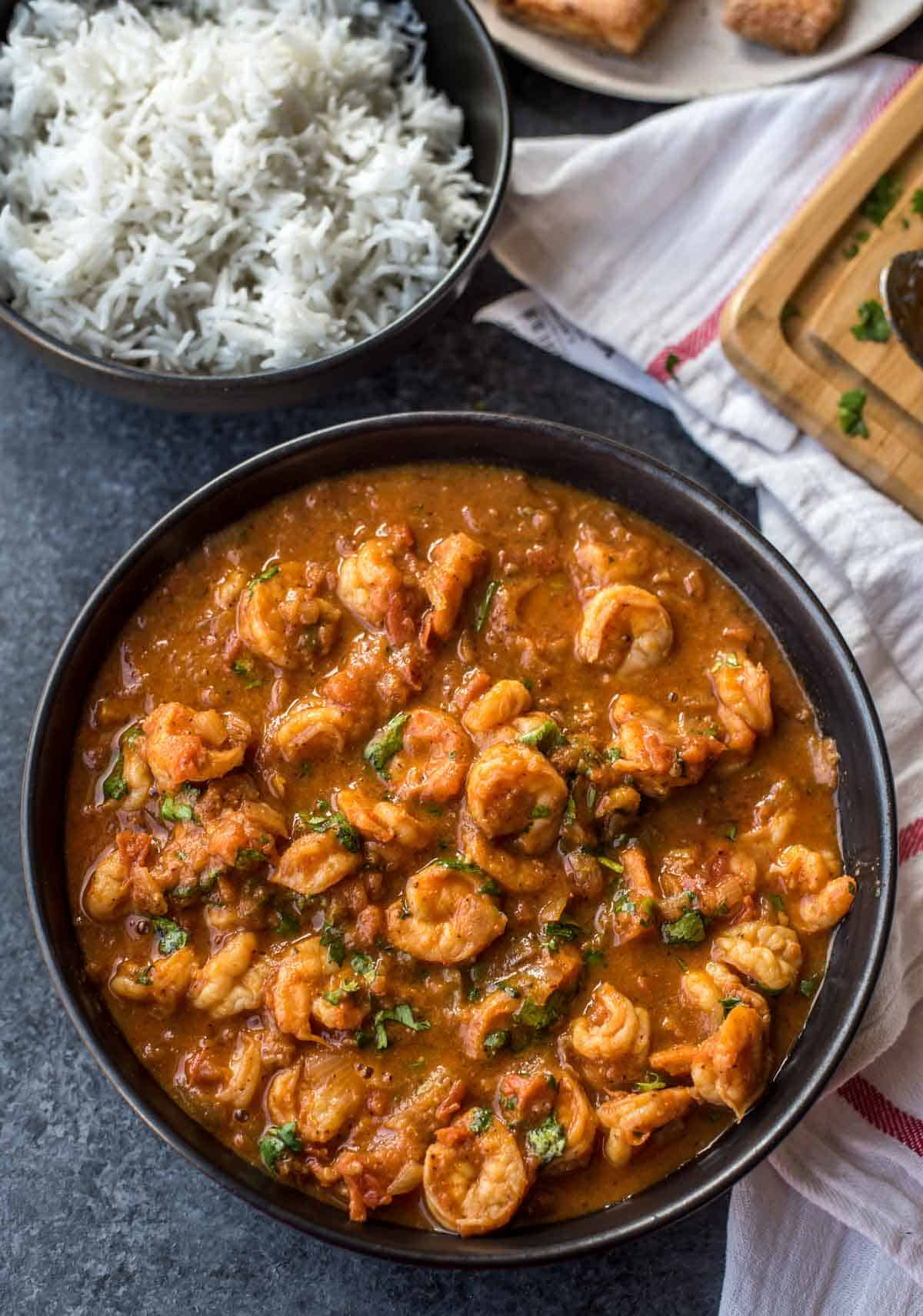 Prawns balchao served in a black bowl alongside rice