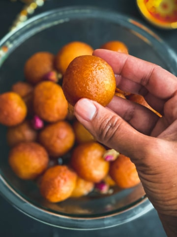 A hand holding a ball of gulab jamun over a glass bowl filled with gulab jamun balls.