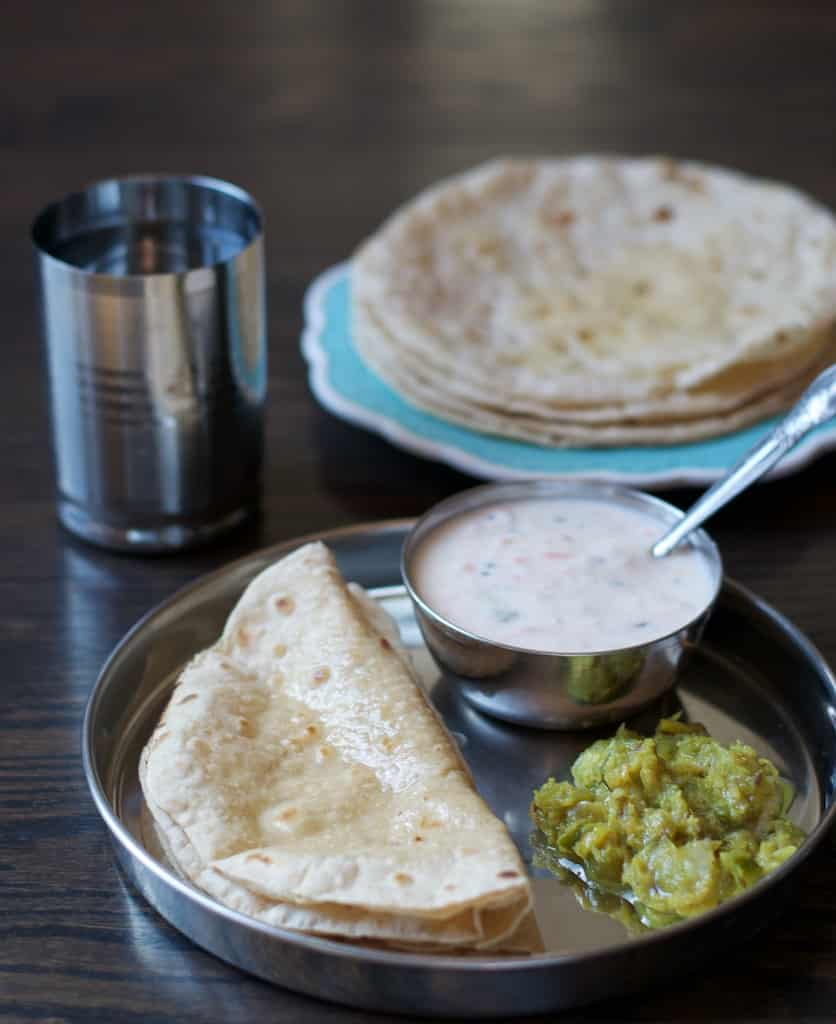 Ghee smeared soft rotis served with raita and a vegetable dish.