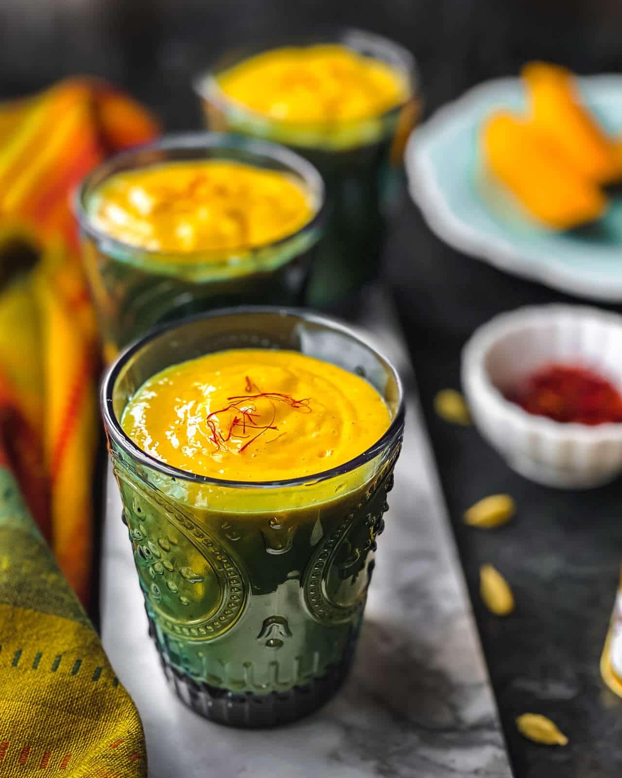 Three glasses of Mango Lassi served on a marble slab