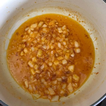 A pot with oil, onion, and garlic chili paste.