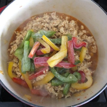 Bell peppers added to the pot of thai basil chicken.