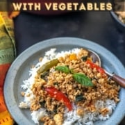 A light blue plate with rice topped with thai basil chicken on a black counter with a red and yellow napkin to the left and the words Thai Basil Chicken with Vegetables.