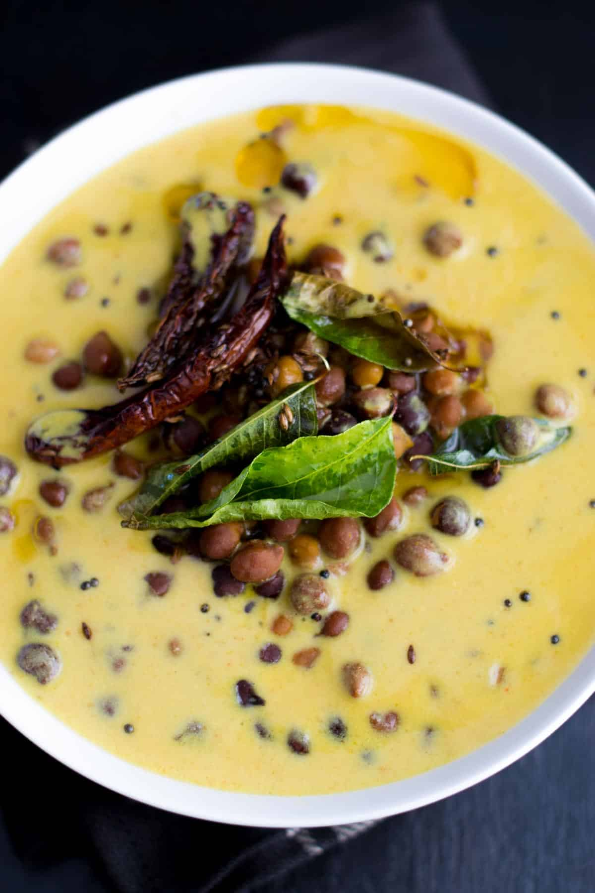 Black chickpeas in a yogurt gravy (Kaale Channe Ki Kadhi) is a Rajasthani dish that is cooked in a spicy yogurt and chickpea (besan) flour gravy. Famously called Jaisalmer Ke Channe, this dish can be made in less than 30 minutes!