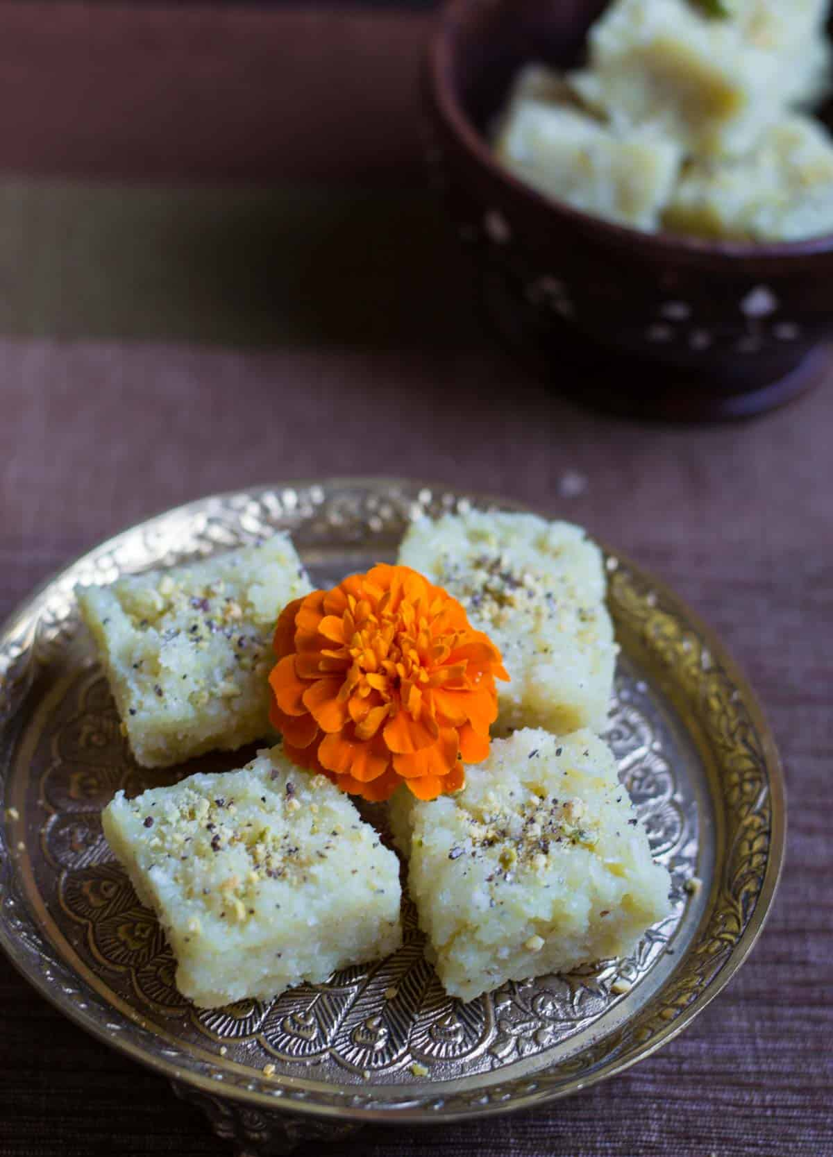 Coconut barfi served on a metal plate