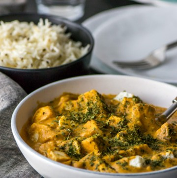 Paneer Makhani served in a white bowl sprinkled with roasted fenugreek leaves
