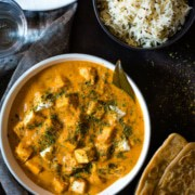 Paneer Makhani served in a white bowl garnished with fenugreek leaves